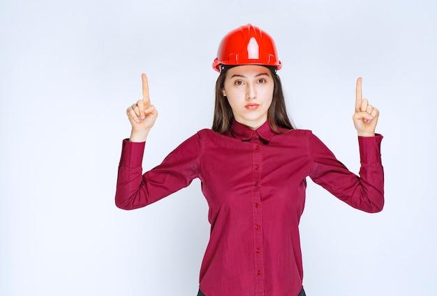 흰색 벽에 서서 포즈를 취하는 빨간 헬멧을 쓴 자신감 있는 여성 건축가.