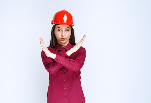Confident female architect in red hard helmet showing stop sign.