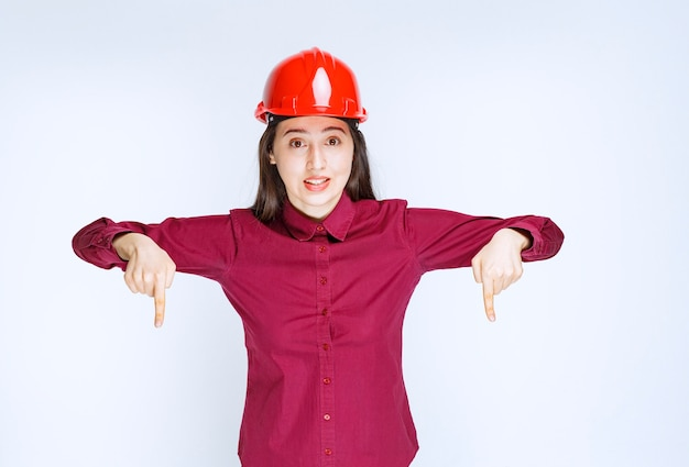 Confident female architect in red hard helmet standing and pointing.