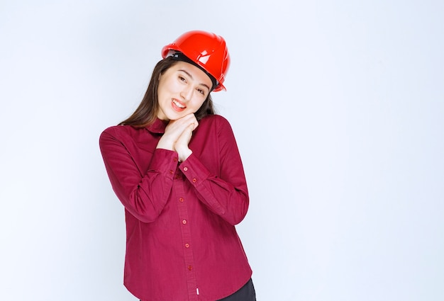 Confident female architect in red hard helmet standing and posing over white wall.