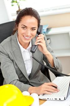 전화로 얘기하고 그녀의 사무실에서 그녀의 노트북을 사용하는 자신감 여성 건축가