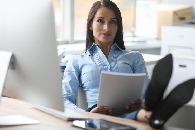 Confident female boss reads report in office.