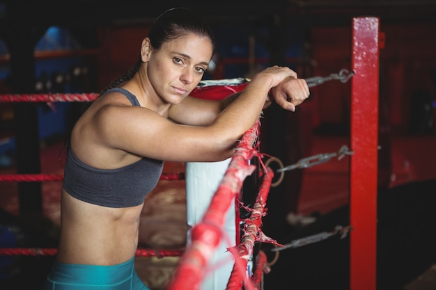 Confident female boxer leaning on boxing ring