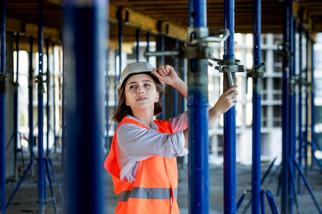 Confident female builder checks fastenings on a monolithic structure. construction concept.