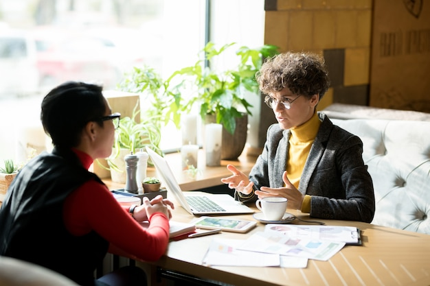 Confident female business analyst sharing report results with co