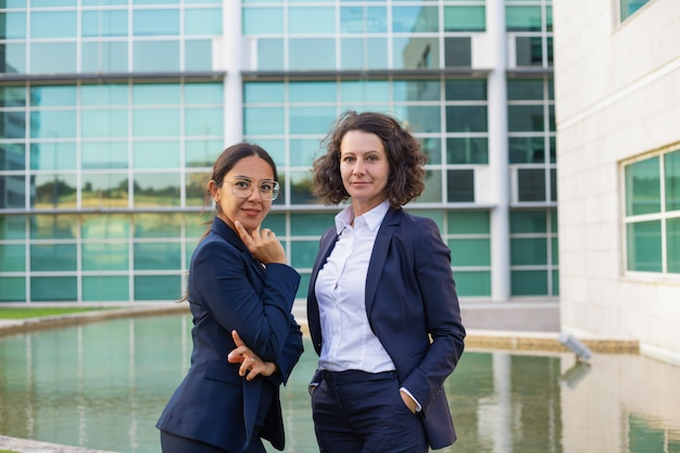 Confident female business professionals posing outside