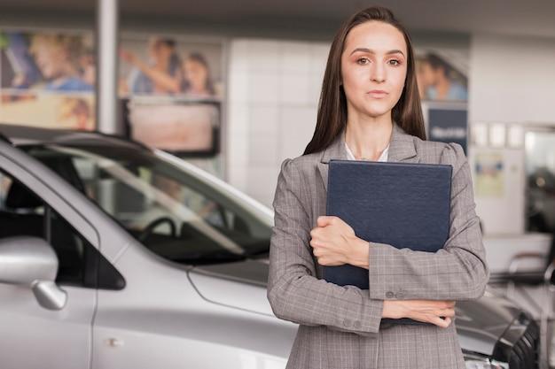 Confident female car dealer looking away