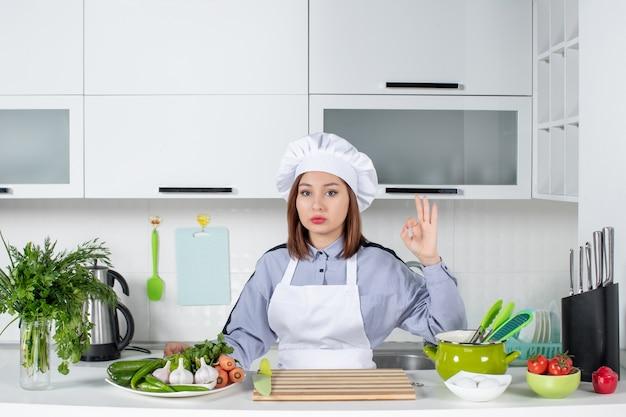 Fiduciosa chef femminile e verdure fresche con attrezzature da cucina e facendo gesti con gli occhiali nella cucina bianca