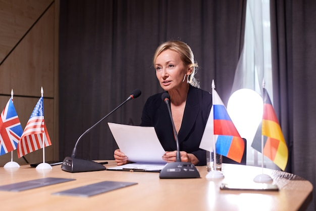 Confident female delegate in formalwear looking at audience, giving speech report at multi-ethnic conference, meeting in boardroom, using microphones