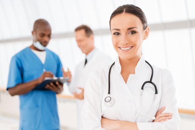 自信のある女医。彼女の同僚がバックグラウンドで話している間、腕を組んで笑顔を保つ美しい女性医師