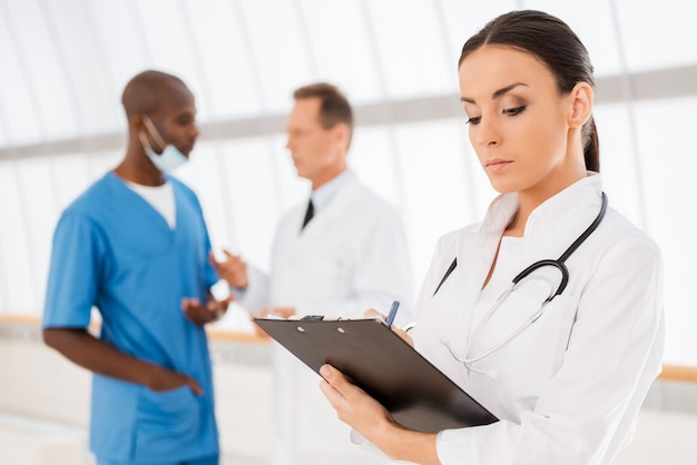 自信のある女医。彼女の同僚がバックグラウンドで話している間、彼女のクリップボードに何かを書いている美しい女性医師