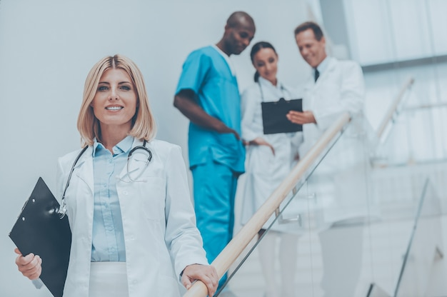 Confident female doctor. confident female doctor moving downstairs and smiling while her colleagues talking in the background