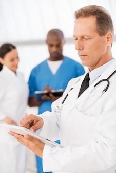 自信のある女医。彼の同僚がバックグラウンドで話している間、デジタルタブレットに取り組んでいる自信のある医師