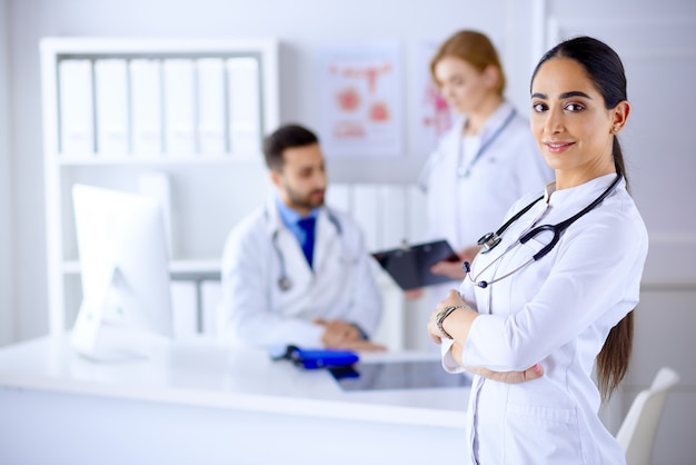 Confident female doctor in front of team, looking smiling, multiracial team with arab female doctor