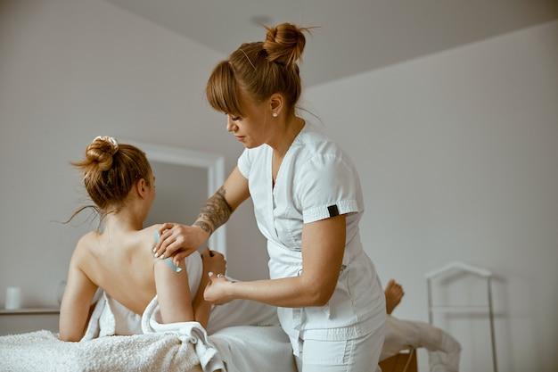 Уверенная женщина-врач делает процедуру тейпирования в кабинете современного лечения