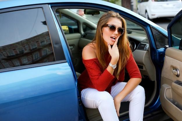 かかとを履いて青いモダンな車に座っている自信のある女性ドライバー。