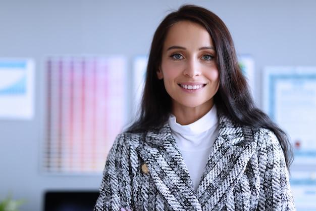 Уверенно работница, улыбаясь в офисе