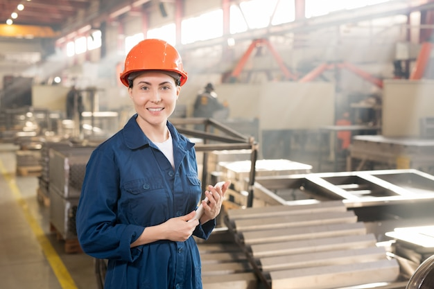 Confident female engineer in blue overalls and orange protective helmet using gadget while working in factory