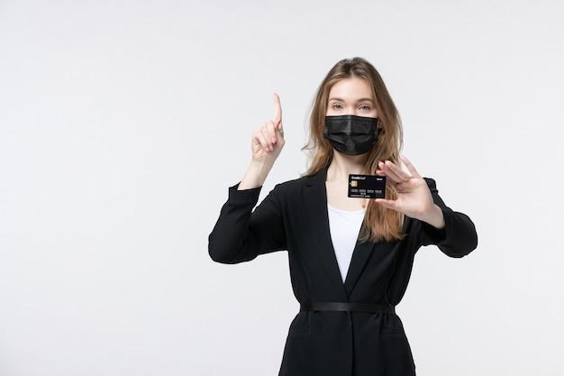 彼女の医療マスクを身に着けて、白で上向きの銀行カードを示すスーツを着た自信のある女性起業家