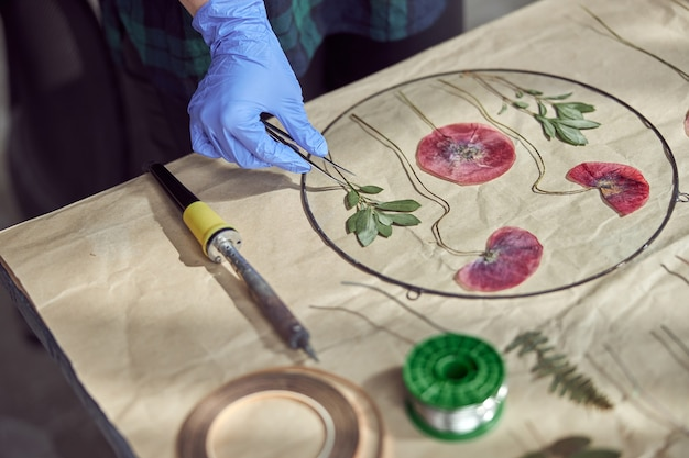 자신감있는 여성 플로리스트가 아늑한 꽃집에서 마른 꽃으로 일하고 있습니다.