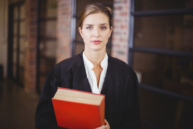 Confident female lawyer with book standing in office
