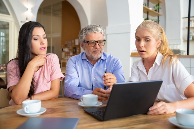 Confident female manager showing presentation on laptop to young woman and mature man, speaking and explaining details