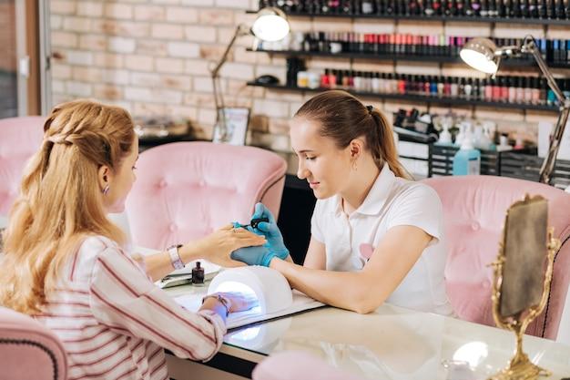 Уверенная женщина-маникюрша наносит лак для ногтей, а женщина лечит ногти под уф-лампой