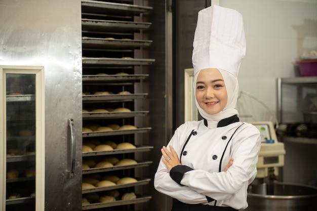 カメラに微笑んで、レストランのキッチンで彼女の腕を組んだ自信を持って女性のイスラム教徒のシェフ