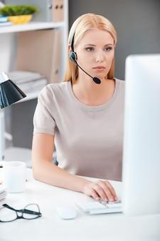 Уверенная женщина-оператор. красивая молодая женщина в наушниках, работающих за компьютером, сидя на своем рабочем месте в офисе
