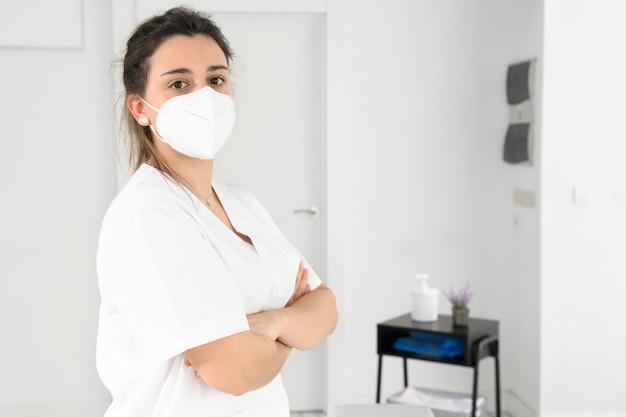 코로나 바이러스 전염병 동안 얼굴 보호 마스크를 쓰고 현대 병원에서 포즈를 취하는 자신감있는 여성 물리 치료사