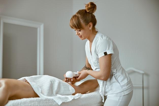 Уверенная женщина-специалист делает антицеллюлитный массаж ног красивой здоровой кавказской клиентке