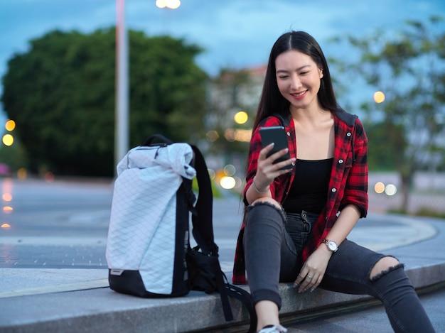 계단에 앉아 스마트폰을 사용하여 택시를 기다리는 자신감 있는 여성 관광 백패커