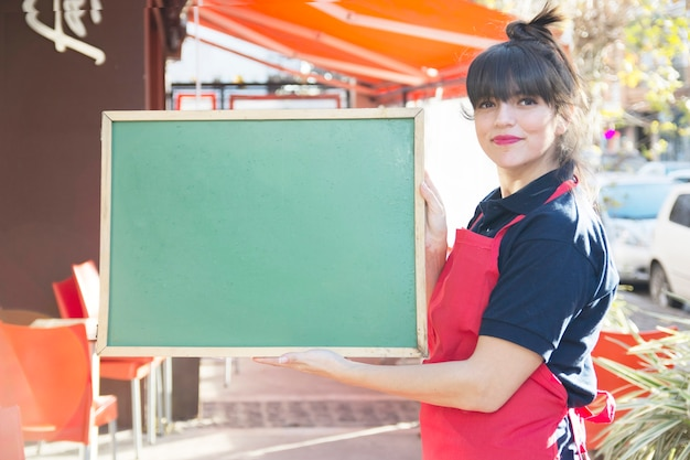 Confident female waitress holding blank green menu board at outdoors