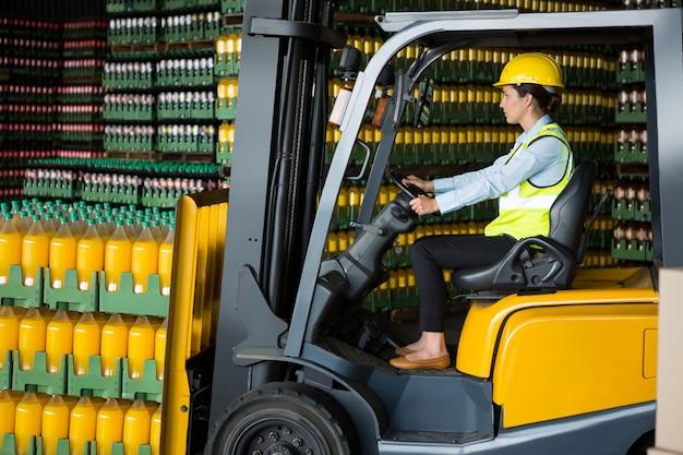 Уверенная женщина-работник за рулем погрузчика на складе
