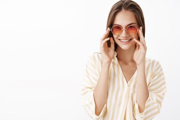 Уверенная в себе женственная и стильная молодая европейка-путешественница в полосатой желтой блузке и модных солнечных очках трогает оправу и радостно смотрит с широкой радостной улыбкой