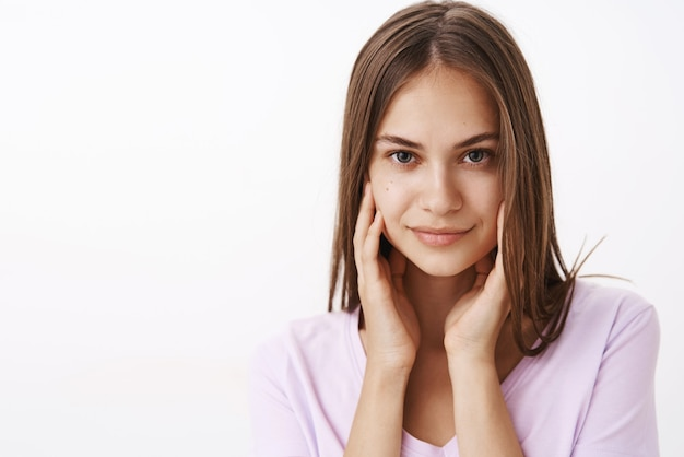 Fiducioso femminile attraente bruna femminile con i capelli lisci e la pelle pulita che tocca il viso delicatamente e sorridente audace flirtare sul muro bianco