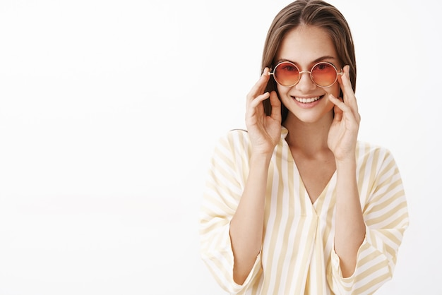 Confident feminine and stylish young european female traveler in striped yellow blouse and trendy sunglasses touching frames and gazing joyfully with broad delighted smile