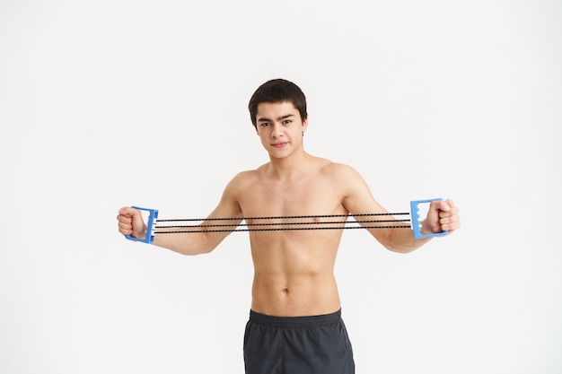 Confident fit young shirtless sportsman doing exercises with expander over white