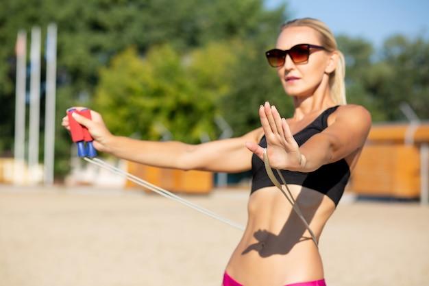 ビーチで縄跳びでストレッチをする完璧なボディを持つ自信のあるフィットネスモデル