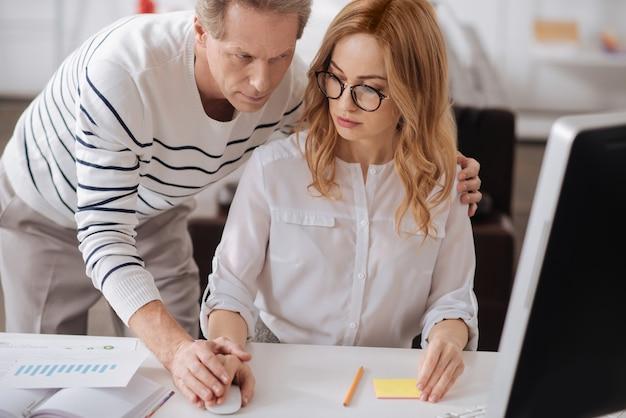 Уверенный флирт пожилого бизнесмена, стоящего в офисе и работающего над проектом, одновременно флиртуя и трогая руку молодого секретаря