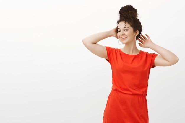 Уверенная кокетливая привлекательная женщина с вьющимися волосами, зачесанными в пучок, в красном платье, держась за руки возле головы