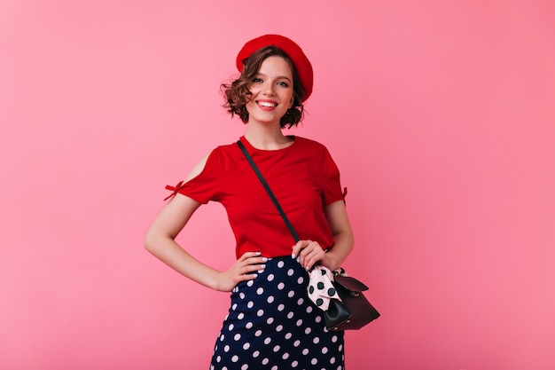 誠実な笑顔でポーズをとる自信のあるフランス人女性。ポジティブな感情を表現する赤いベレー帽のロマンチックな白人女性。