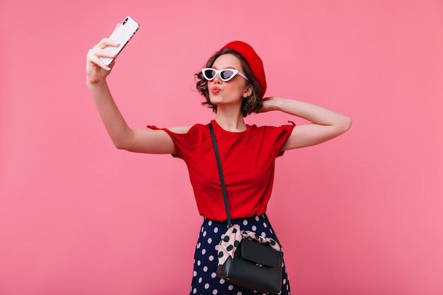 キスの表情でポーズをとる自信のあるフランス人女性。セルフィーを作りながら愛を表現する赤いベレー帽の素敵な女性モデル。