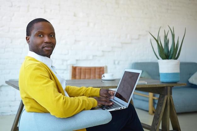 자에 편안하게 앉아, 집에서 전자 기기를 사용하여 온라인 쇼핑, 카메라를 응시하는 세련된 옷을 입고 자신감이 친절한 찾고 젊은 혼혈 남자. 기술, 라이프 스타일 및 기기