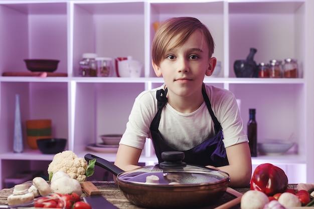 부엌에서 자신감 미래 요리사입니다. 요리사 앞치마를 입은 소년. 요리 음식 개념입니다. 저녁 식사를 위해 건강식을 준비하는 아들. 소년은 전문 요리사가되고 싶어합니다. 팬과 많은 야채가 있는 테이블.