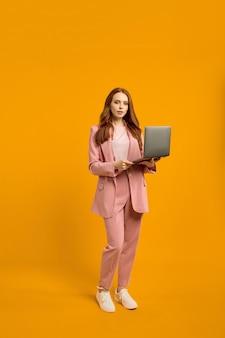 Уверенная рыжая дама идет с ноутбуком на ярко-желто-оранжевой спине студии ...