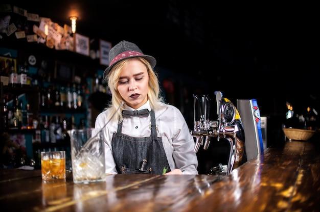 Уверенная девушка-бармен наливает свежий алкогольный напиток в бокалы в баре