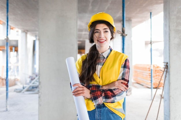 Confident girl engineer builder stands at a construction site holding paper with drawings