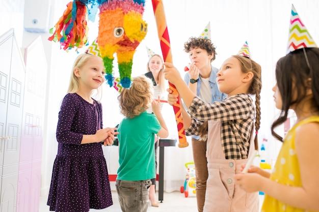 子供のお祝いでカラフルなピニャータを打つ自信を持って女の子