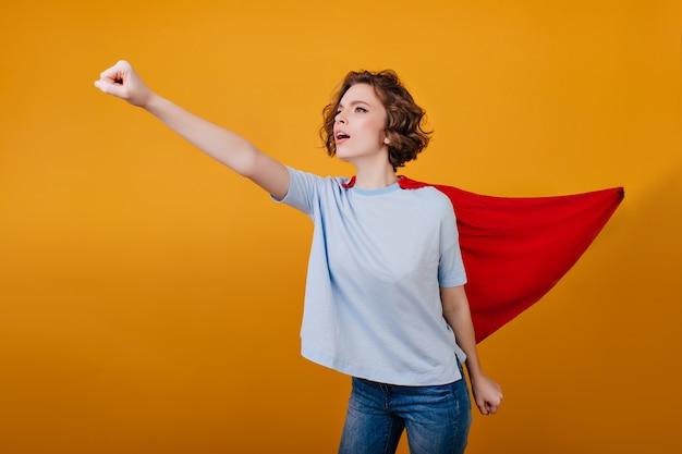 Fiduciosa ragazza in mantello rosso divertirsi durante il servizio fotografico